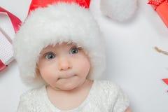 Bébé se trouvant avec des présents dans le chapeau de Santa sur le fond blanc Image libre de droits