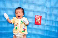 Bébé se trouvant avec l'enveloppe rouge chinoise photos stock