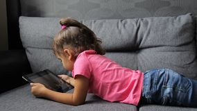 Bébé se trouvant sur le sofa avec le comprimé Jouer menteur de petite fille sur le comprimé banque de vidéos