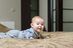 Bébé se trouvant sur le ventre et grimaçant Image stock