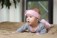 Bébé se trouvant sur le ventre et grimaçant Images stock