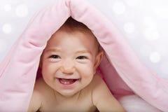 Bébé sous la couverture rose avec le sourire Photographie stock libre de droits