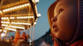 Bébé stupéfait regardant le rétro carrousel lumineux le soir image libre de droits
