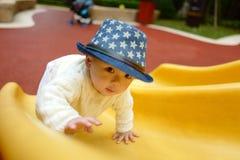 Bébé sur la glissière de terrain de jeu Photo libre de droits