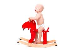 Bébé sur le cheval ou les élans de jouet Image stock
