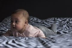 Bébé sur le ventre dans le lit photo libre de droits