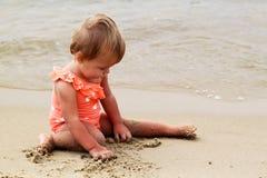 Bébé sur une plage de sable Photos libres de droits