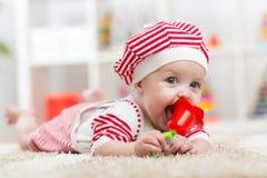 Bébé tenant un jouet et se trouvant sur le ventre dans la crèche Images stock