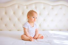Bébé triste dans la chambre à coucher ensoleillée blanche Photos stock