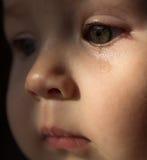 Bébé triste de visage Une larme sur le visage images stock
