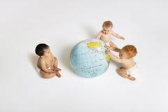Bébés jouant avec le globe Image stock