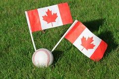Béisbol con las banderas canadienses en un campo de hierba Major League Baseball fotos de archivo libres de regalías