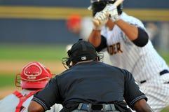 Béisbol de la liga menor - el árbitro mira la echada Fotografía de archivo