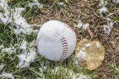 Béisbol en el campo herboso cubierto en la polvoreda ligera de la nieve Fotos de archivo libres de regalías