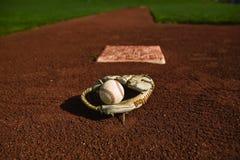 Béisbol en guante en el campo Foto de archivo libre de regalías