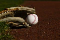 Béisbol en guante en el campo Fotos de archivo