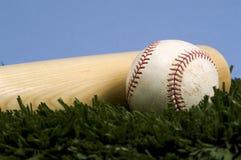 Béisbol en hierba con el palo contra el cielo azul Imágenes de archivo libres de regalías