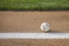 Béisbol en la trayectoria baja con el área de la pista de aterrizaje de la hierba Fotos de archivo