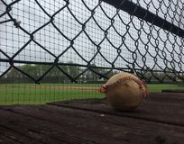 Béisbol gastado en cubierta de madera sobre campo de béisbol imágenes de archivo libres de regalías