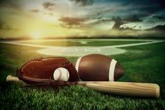 Béisbol, palo, y mitón en campo en la puesta del sol Fotos de archivo libres de regalías