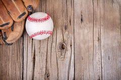 Béisbol y mitón en fondo de madera Foto de archivo