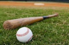 Béisbol y palo en campo Fotografía de archivo libre de regalías
