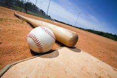 Béisbol y palo en la placa casera Fotos de archivo