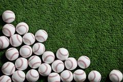 Béisboles en un fondo verde del césped Fotos de archivo
