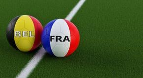 Bélgica contra Fósforo de futebol de França - bolas de futebol em cores nacionais de Bélgica e de França em um campo de futebol Fotografia de Stock Royalty Free