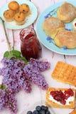 Bélgica recientemente cocida se enrolla en la tabla de madera romántica con las flores de la lila Foto de archivo libre de regalías