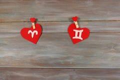 Bélier et jumeaux signes du zodiaque et de coeur Backgroun en bois Images stock