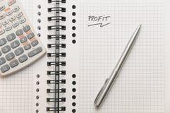 Bénéfice écrit sur le carnet de notes à spirale blanc Photos libres de droits