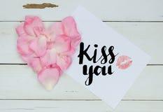 Bésele mensaje con el corazón de los pétalos color de rosa y del beso del lápiz labial Fotos de archivo libres de regalías
