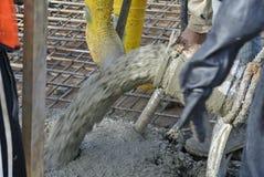 Béton coulé de travailleurs de la construction utilisant le tuyau concret Image stock