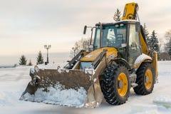 Bêcheur stationnaire jaune de JCB dans la neige Images libres de droits