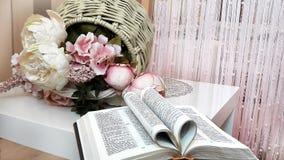 A Bíblia aberta e uma cesta das flores na tabela foto de stock