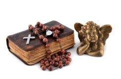 A Bíblia com grânulos e um anjo Imagens de Stock