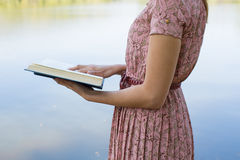 A Bíblia da leitura da jovem mulher no parque natural Imagem de Stock Royalty Free