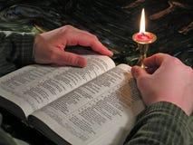 A Bíblia da leitura pela luz de vela fotos de stock royalty free