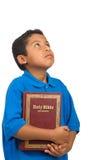 A Bíblia da terra arrendada da criança e vista acima Imagens de Stock
