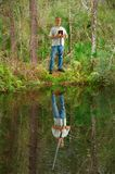 A Bíblia da terra arrendada do homem quando sua reflexão na água o mostrar que guarda uma espada que representa o poder da fé foto de stock royalty free