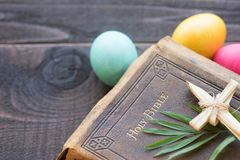 A Bíblia de couro do vintage com cruz da grama, folhas de palmeira, ovos da páscoa coloridos no fundo de madeira rústico escuro d Imagens de Stock Royalty Free