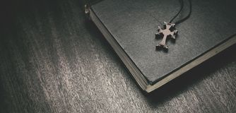 A Bíblia e cruz em um fundo de madeira imagem de stock