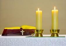 A Bíblia em velas ardentes da igreja fotos de stock