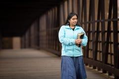 A Bíblia latino-americano da terra arrendada da mulher ao andar na ponte imagens de stock