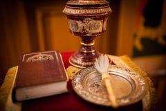 A Bíblia ortodoxo, cruz e uma mecha em um pano para o batismo imagens de stock