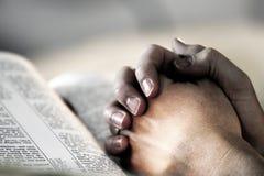 A Bíblia Praying das mãos Fotos de Stock