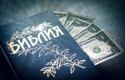 A Bíblia Sagrada cirílica com dólares do dinheiro foto de stock