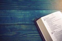 A Bíblia Sagrada em uma tabela de madeira azul fotografia de stock