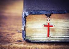 A Bíblia Sagrada velha com cruz do res do metal Imagens de Stock